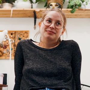 En ung kvinna sitter klädd i jeans och grå tröja vid en sängkant.