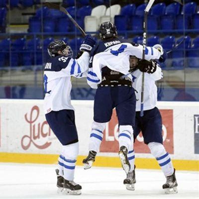 Blåvita finländska ishockeyspelare firar mål i förlängningen genom att kramas.
