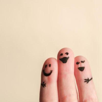 kolme sormea, joihin piirretty naamat