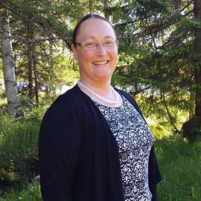 Kuvassa Eva-Maria Strömsholm metsämaisemassa.