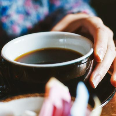 Kahvikuppi kädessä.