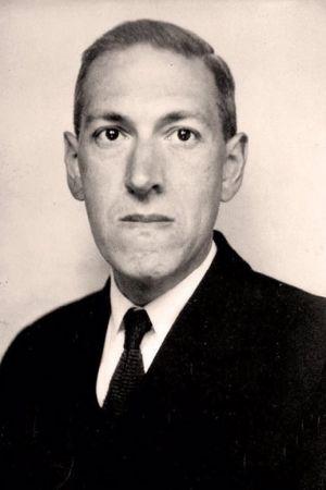 Ett svartvitt foto av en man med avlångt ansikte, överrock och slips som tittar in i kameran