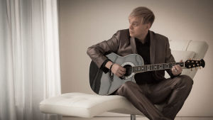 promofoto på Kurre Westerlund som sitter och spelar på gitarr.