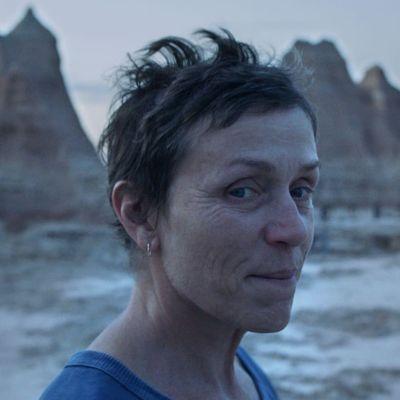 Nainen seisoo erämaassa, vuoristo taustalla.