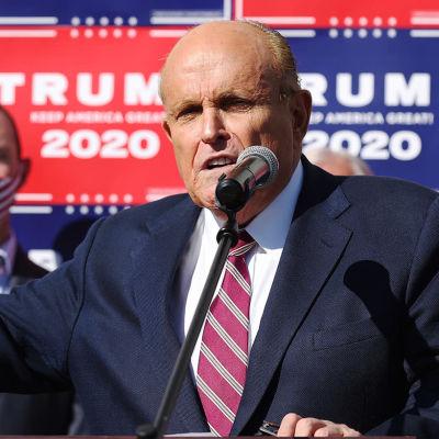 Man i blå kostym och rödrandig slips står framför vägg där det står Trump 2020.
