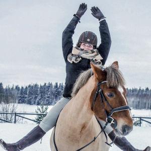 En ung kvinna sitter på en häst. Hon sträcker upp händerna i luften och fötterna åt sidorna.