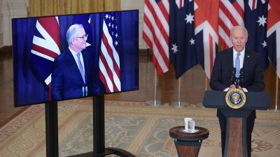 USA:s president Joe Biden vid ett podium i Vita huset medan Australiens premiärminister Scott Morrison syns på en tv-skärm bredvid honom.