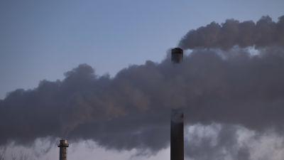 Rökmoln som bolmar ut ur ett av Fortums värmekraftverks pipor.