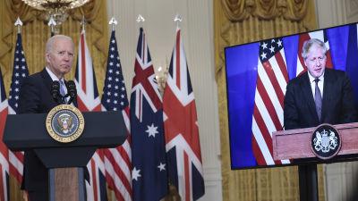 Joe Biden vid ett podium i Vita huset med Boris Johnson på en tv-skärm bredvid honom.