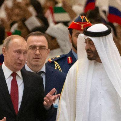 Vladimir Putin med Abu Dhabis kronprins Mohammed bin Zayed al-Nahyan spatserar på en blå matta. I bakgrunden syns Abu Dhabis flagga och till vänster i bilden syns Rysslands flagga.