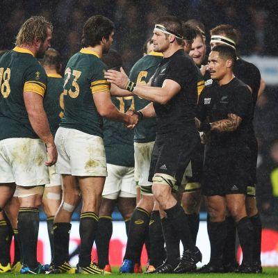 Etelä-Afrikan pelaajat onnittelevat Uuden-Seelannin joukkuetta voitosta rugbyn MM-välierän jälkeen.
