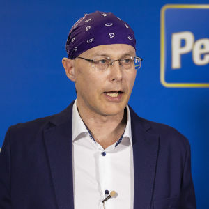Bild på man med glasögon och bandana på huvudet som håller ut händerna.