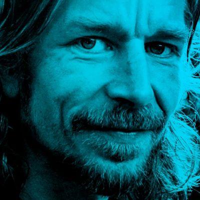 Karl Ove Knausgård katsoo kameraan siniseksi värjätyssä kuvassa.