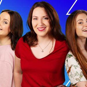 Tre tjejer står och ler framför en blå bakgrund