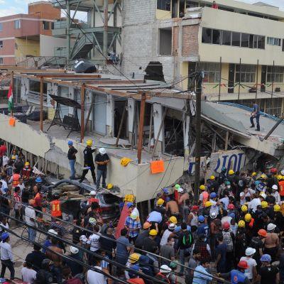 Osin romahtanut koulurakennus. Paljon pelastusväkeä paikalla.