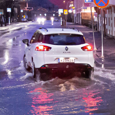 Bil kör i enorm vattenpöl, slangar pumpar ut vatten ur höghuskällare