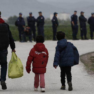 Aikuinen mies ja kaksi lasta, kävelevät tietä pitkin, kaikki selin kameraan, miehellä selässään kantamuksia. Taustalla, epätarkkana rivi poliiseja tien reunalla.