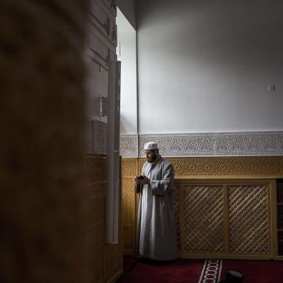 Mies seisoo moskeijan käytävällä ja tutkii matkapuhelintaan.