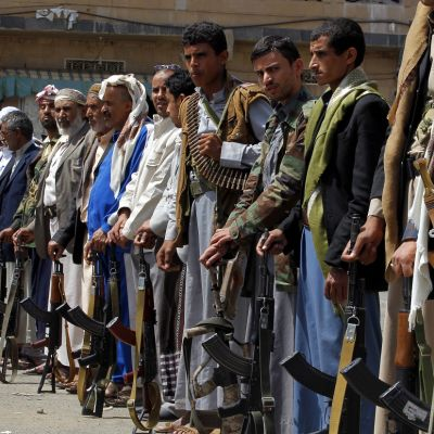 Jemenin huthikapinallisia tukevia miehiä seisoo rivissä, kiväärit maata vasten nojaten.