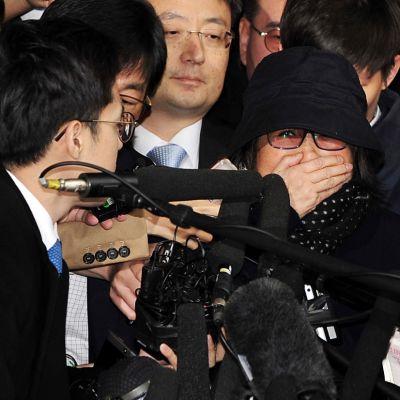 Presidentin avustaja Choi Sun-sil viranomaisten ympäröimänä. Choi on peittänyt suunsa kädellään, ympärillään toimittajajoukko.