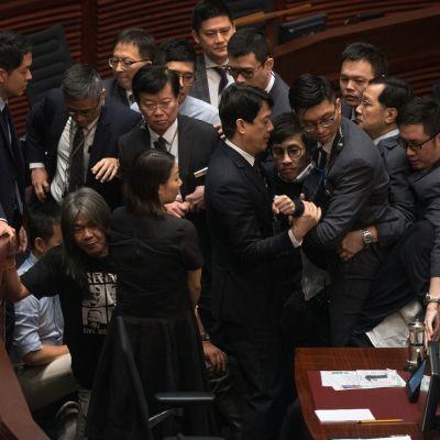 Kapinaoiva kansanedustaja Baggio Leung  turvamiesten keskellä, häntä ollaan siirtämässä pois istuntosalista.