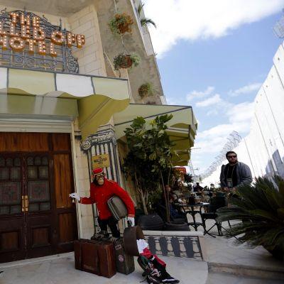 Hotellin sisäänkäynti, jossa seisoo portieeria markkeeraava apinapatsas matkalaukkujen päällä.