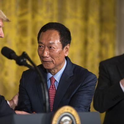Trump myhäilevä ilme kasvoillaan. Kättelee Foxconnin taiwanilaista perustajaa.