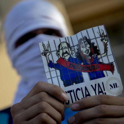 Nuori mies kädessään presidentti Daniel Ortegan ja tämän vaimon Rosario Murillon piirroskuva