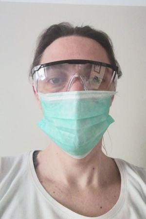 En läkare med andningsmask och skyddsglasögon.