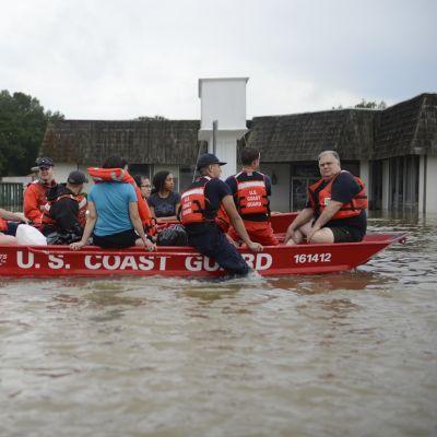 Evakuoitavia ihmisiä istuu veneessä.