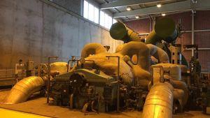 Den gamla delen av anläggningarna vid Vaskiluodon Voima. Inne i fabriksbyggnad, rör och maskiner.