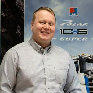 En man står och ler framför en reklambild av ett Sisu Polar-fordon.