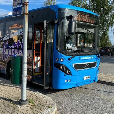 Kuvassa bussi, joka odottaa bussipysäkillä