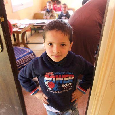 Poika seisoo kädet puuskassa luokan ovella.