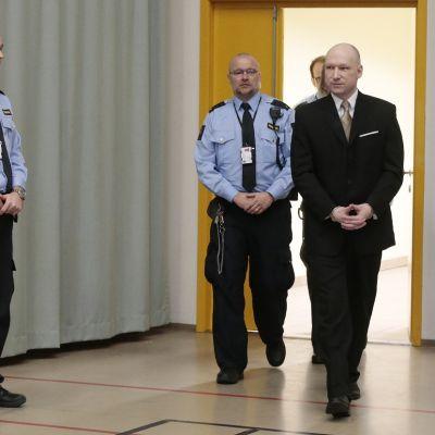 Breivik saapuu saliin puku päällä, taustalla vartijoita.