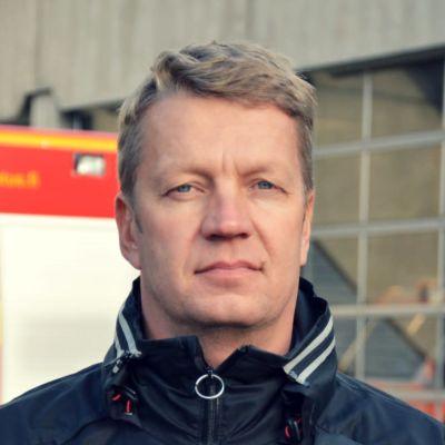 Knut Lehtinen framför en brandbil som står parkerad framför pargas brandstation.