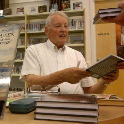 Olavi Koivukangas signeeraa lukijankappaleita Titanic-kirjan julkistamistilaisuudessa Ylihärmässä