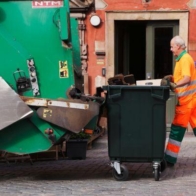Harmaahiuksinen roska-auton kuljettaja työssä.