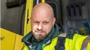 En man med rakat huvud och skägg som har på sig gröna kläder och gul reflexjacka. Det står HUS Kenttäjohtaja Janne Keto i höjd med bröstficka på jackan.