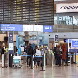 Matkustajia lentoaseman lähtöaulassa