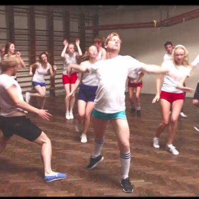 Ett gäng som dansar i en gymnastiksal.