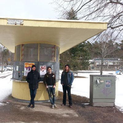 Keltainen Käpylän lippakioski. Edessä seisoo kolme miestä.