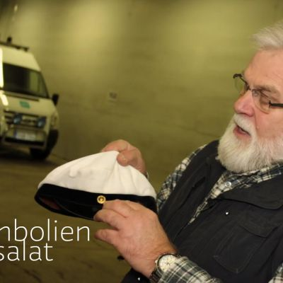 Professori Reijo Heikkinen pitelee käsissään ylioppilaslakkia.