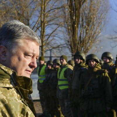 Harmaahiuksinen mies armeijan vaatteissa, hänen edessä miehiärivissä kypärät päässä.