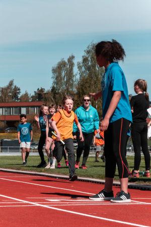 En stafettrace. Två barn springer mot ett tredje som väntar på den enas stafettpinne.