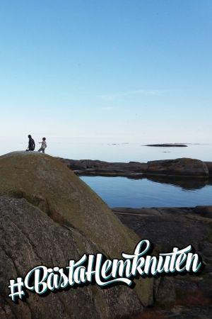 Två personer på avstånd på en klipphäll vid havet