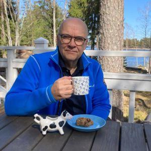 En man med en kaffemugg sitter nära havet.