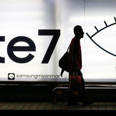 Mies kävelee Samsung Galaxy Note 7:n mainoksen ohi.