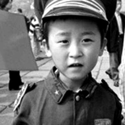 Pieni poika Kiinan lippu kädessään.