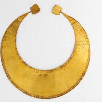 Kullasta taottu puolikuun muotoinen levy, jossa on siksak-kuviointia
